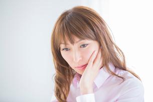 頬に手を当てる女性の写真素材 [FYI01428449]