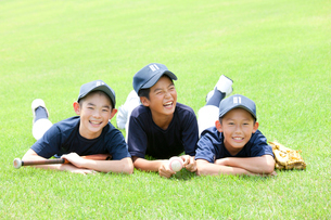 芝生に寝転ぶ小学生の野球少年の写真素材 [FYI01428531]