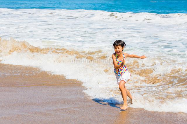波打ち際で遊ぶ水着の女の子の写真素材 [FYI01428552]