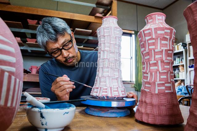 素焼きの陶器に絵付けする陶芸家の写真素材 [FYI01428750]