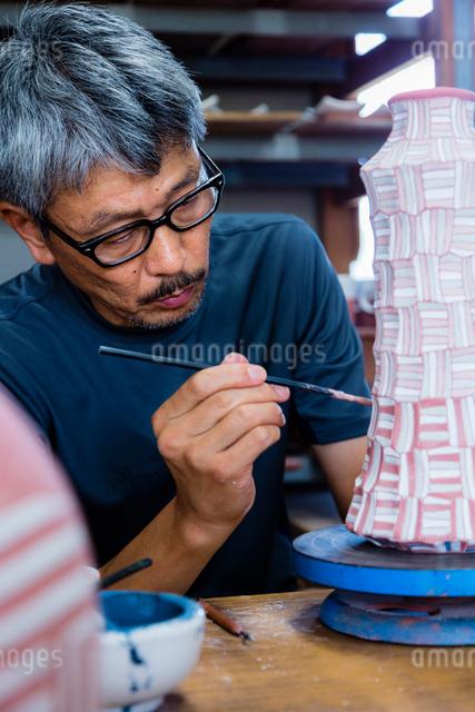 素焼きの陶器に絵付けする陶芸家の写真素材 [FYI01428778]