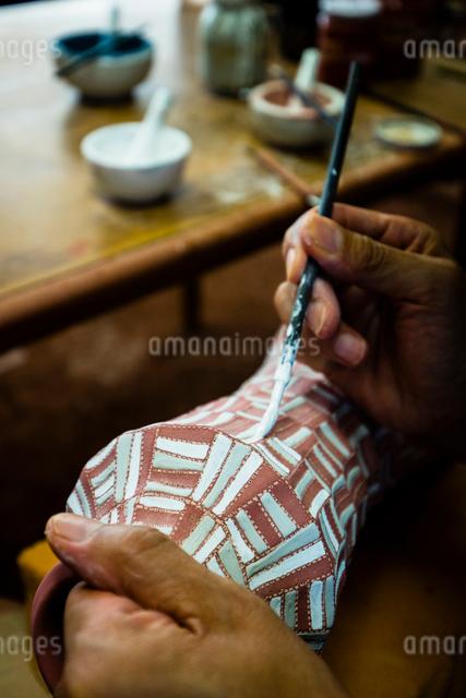 素焼きの陶器に絵付けする陶芸家の手の写真素材 [FYI01428791]