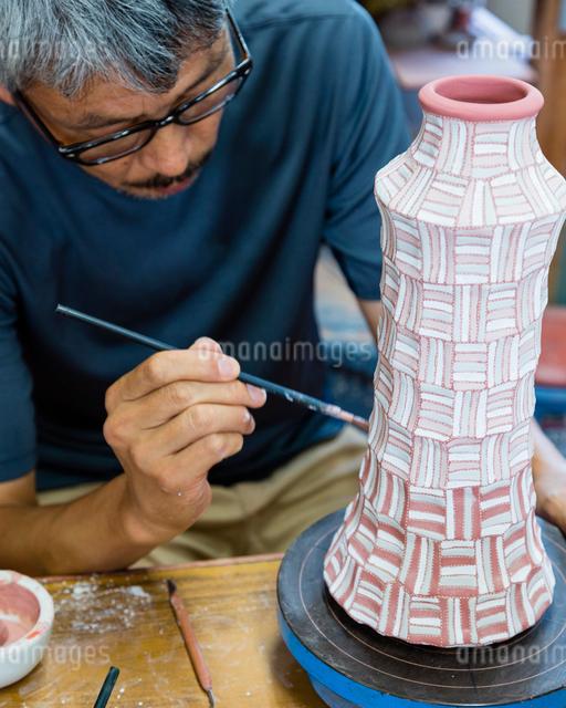 素焼きの陶器に絵付けする陶芸家の写真素材 [FYI01428827]