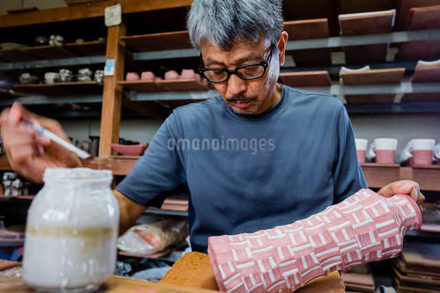 素焼きの陶器に絵付けする陶芸家の写真素材 [FYI01428886]