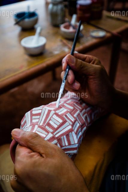 素焼きの陶器に絵付けする陶芸家の手の写真素材 [FYI01428911]