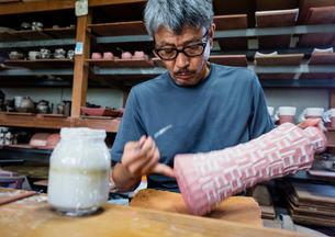 素焼きの陶器に絵付けする陶芸家の写真素材 [FYI01428917]