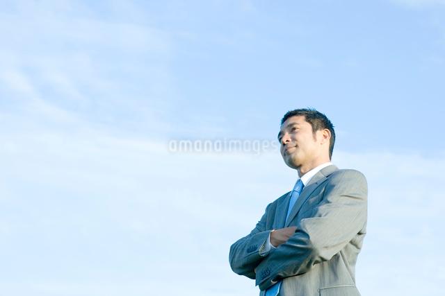 腕を組んで見つめるビジネスマンの写真素材 [FYI01429558]