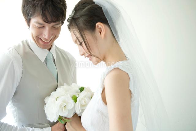 ブーケを一緒に持つ笑顔の新郎新婦の写真素材 [FYI01429760]