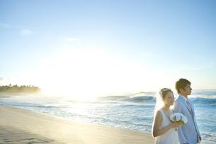 夕暮れの海岸を背に砂浜を歩く新郎新婦の写真素材 [FYI01429778]