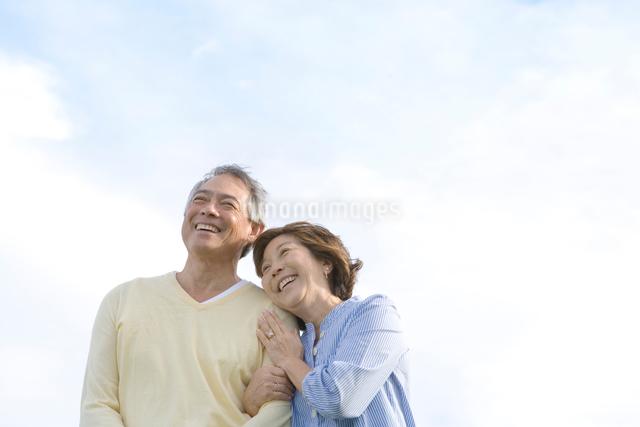 青空の下で寄り添うシニア夫婦の写真素材 [FYI01429908]