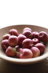 木製の器に入ったひめりんごの写真素材 [FYI01429933]
