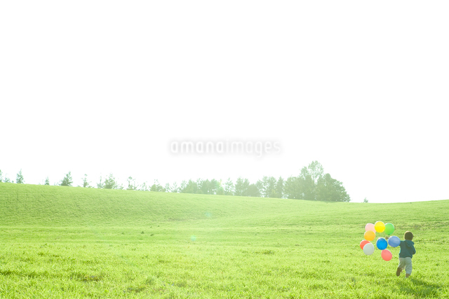 草原で風船を持って走る少年の写真素材 [FYI01430002]