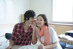 教室で内緒話をするカップルの写真素材 [FYI01430006]
