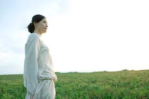 草原に立ち景色を眺める30代女性の横顔の写真素材 [FYI01430165]