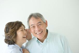 笑顔で耳打ちするシニア夫婦の写真素材 [FYI01430172]