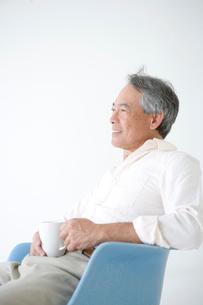 椅子に座りコーヒーカップを手に持つ60代男性の写真素材 [FYI01430262]