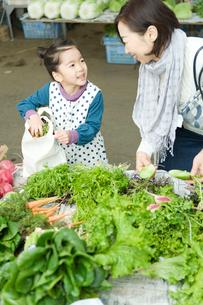 野菜市場で買い物をする孫娘と祖母の写真素材 [FYI01430393]