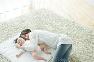 カーペットの上で一緒にお昼寝をする母親と赤ちゃんの写真素材 [FYI01430530]