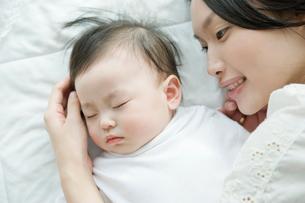眠っている赤ちゃんを見つめる母親の写真素材 [FYI01430573]