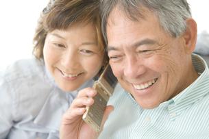 携帯電話で話すシニア夫婦の写真素材 [FYI01430592]