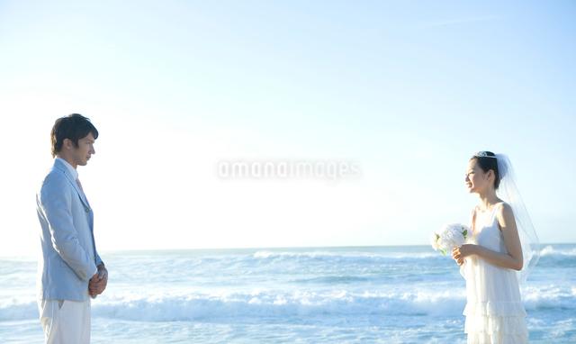 夕暮れの海を背に向かい合う新郎新婦の写真素材 [FYI01430602]