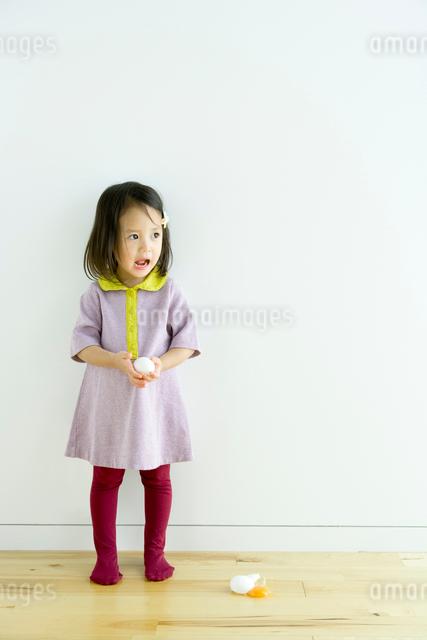 床に生卵を落とし驚く少女の写真素材 [FYI01430652]