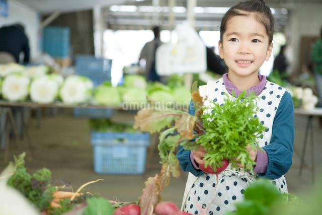 市場の野菜を手に取る女の子の写真素材 [FYI01430670]