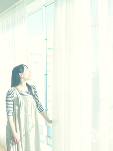 カーテンを開け窓の外を眺める10代女性の写真素材 [FYI01430847]