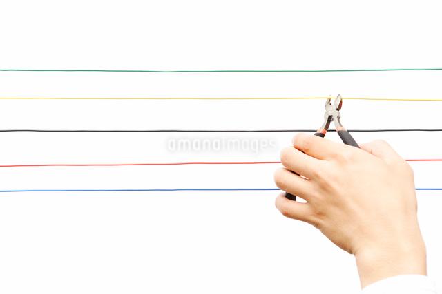 カラフルなコードとペンチを持つ手の写真素材 [FYI01430882]