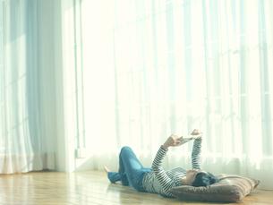 部屋で仰向けになり本を読む10代女性の写真素材 [FYI01430999]