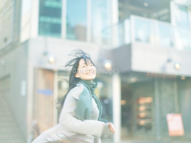 街中を笑顔で走る10代女性の写真素材 [FYI01431041]