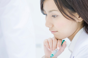 ペンを持ち考える白衣の女性の横顔の写真素材 [FYI01431502]
