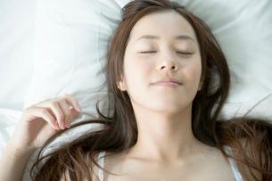 ベッドで眠る20代女性の写真素材 [FYI01431516]