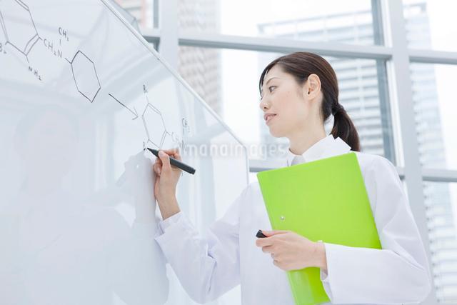 ホワイトボードで説明する白衣の30代女性の写真素材 [FYI01431811]