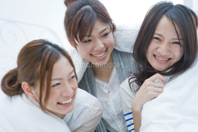 シーツに包まって笑う20代女性3人の写真素材 [FYI01431829]