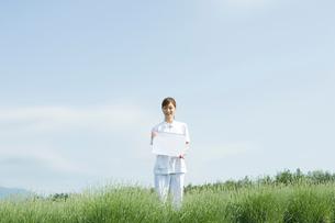 メッセージボードを持つ20代の女性介護士の写真素材 [FYI01431984]