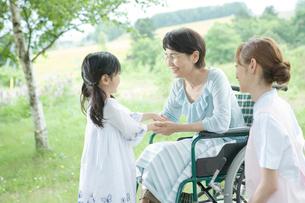 孫の手を握る60代の女性と見守る女性介護士の写真素材 [FYI01432089]