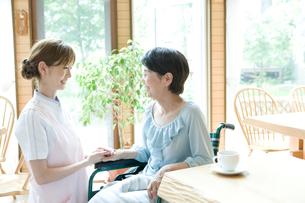 向かい合う20代の介護士と60代の女性の写真素材 [FYI01432131]