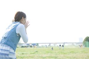 草野球の試合の応援をする20代女性の後姿の写真素材 [FYI01432354]