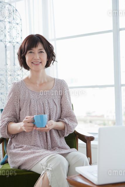 パソコンの前に座りほほえむ40代女性の写真素材 [FYI01432434]
