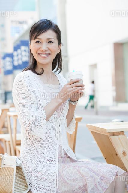 オープンカフェでコーヒーを飲む50代の女性の写真素材 [FYI01432478]