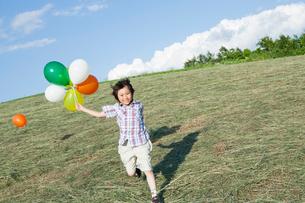 風船を持って走る男の子の写真素材 [FYI01432517]