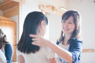 鏡台の前でほほえむ母と娘の写真素材 [FYI01432525]