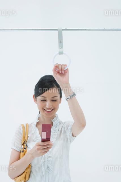 電車のつり革につかまり携帯電話を見る女性の写真素材 [FYI01432582]
