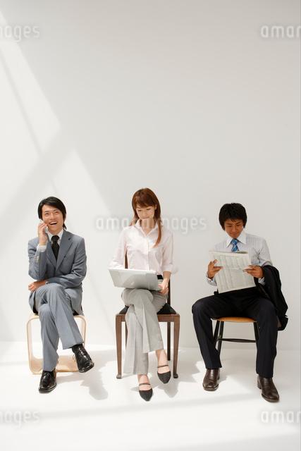 椅子に座るビジネスマンとビジネスウーマンの写真素材 [FYI01432778]