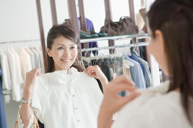 鏡の前で洋服をあてる50代の女性の写真素材 [FYI01432865]