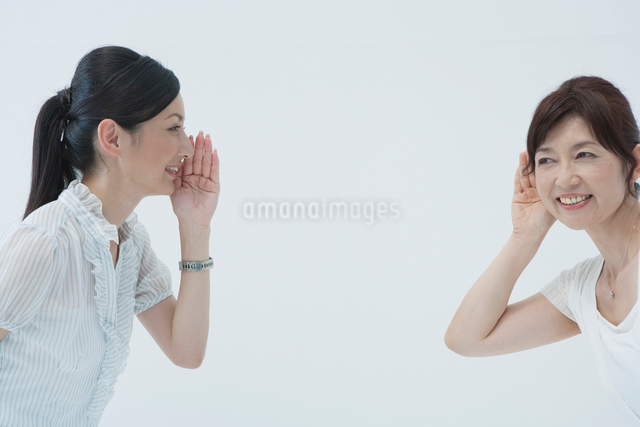 耳打ちで話す女性2人の写真素材 [FYI01432867]