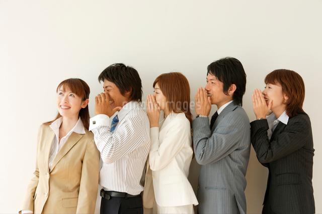 耳打ちをするビジネスマンとビジネスウーマンの写真素材 [FYI01432920]