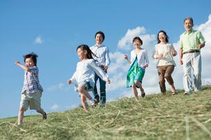 丘を歩く三世代家族の写真素材 [FYI01432995]