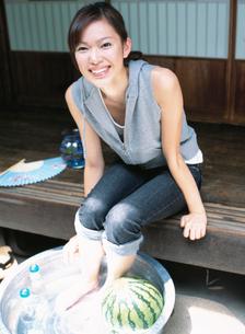 縁側に座りスイカとラムネを冷やす日本人女性の写真素材 [FYI01433097]